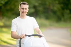 Portrait of happy dad with pram in park Stock Photos
