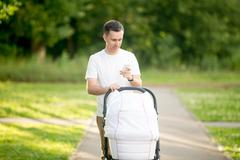Man with baby carriage in park looking at phone screen Stock Photos