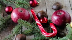Apples, fir and red Christmas baubles with lights bokeh and Merry Christmas wish Stock Footage