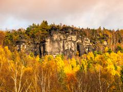 Sandstone rock formation in the middle of autumn forest Stock Photos