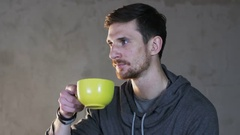 Young Man Drinks Tea From a Green Cup Stock Footage
