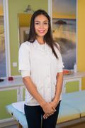 Smiling beauty therapist standing beside massage table at the spa and welcomes Stock Photos
