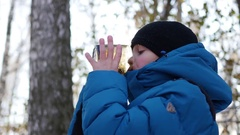 The child is drinking hot tea from a mug in the winter outdoor. Sunny day Stock Footage