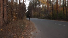 A girl walking along the roadside. And getting out of the frame Stock Footage