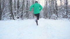Slow Motion Young Sportsman Running Through Snowy Forest. Training and exerci Stock Footage