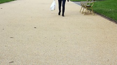 Young adult woman walking in park with carrier bag Stock Footage