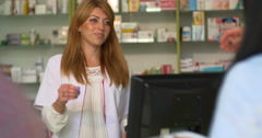 Young attracting female pharmacist selling pills to customer at pharmacy Stock Footage
