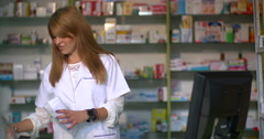 Young attracting female pharmacist packaging medicine Stock Footage