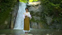 Traditional dressed singer singing next to a waterfall Stock Footage