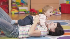 Young Mother Holding Her little baby son in the room lying on the floor. Stock Footage