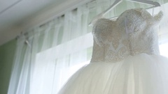 Incredible white wedding dress with a full skirt on a hanger in the room of the Stock Footage