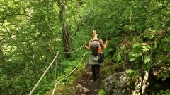 Woman hiker with backpack walking on the wild track in mountain forest. Norway Stock Footage