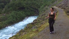 Woman hiker with backpack walking on the wild track near Vettisfossen waterfall Stock Footage