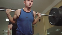Athletes perform exercises a squats with a barbell in the gym with the trainer Stock Footage