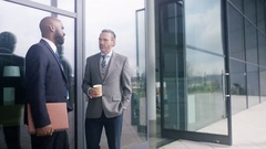 4K Businesswoman with bicycle leaving office building & talking to coworkers Stock Footage