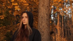 A girl in a hoody with her hair loose standing by a tree in an autumnal forest Stock Footage