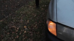 The front turn signal of a car on the roadside blinking, and a part of the car Stock Footage