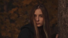 A girl in a hoody with her hair loose to hide a part of her face looking Stock Footage