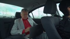 Portrait male working on the computer in car Stock Footage