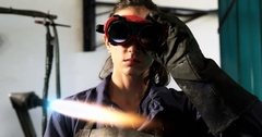 Female welder welding a metal Stock Footage