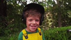 A young boy in a batter's helmet mugs for the camera. Slow motion. Stock Footage