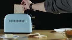 Man Puts Two Loaves of Bread Into an Electric Toaster Stock Footage