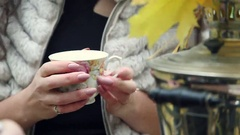 Girl warms the hands, holding a cup of hot tea Stock Footage