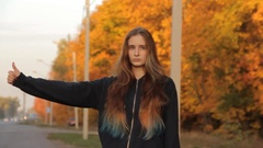 A girl with her hand raised hitchhiking thumb up . A highway with unfocesed cars Stock Footage