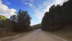 POV car vehicle driving narrow mountain road wet countryside trees sunny sky Stock Footage
