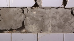 DOLLY: Cracked ceramic tiles falling off from the wall in bathroom or kitchen Stock Footage