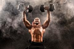 Topless muscular man doing dumbbell exercise on bench press Stock Photos