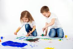 Sister and brother painting using bright colors, brushes Stock Photos