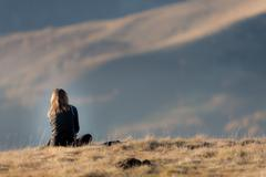 Rear view of girl sitting in a mountain meadow in fall season at sunset. Larg Stock Photos
