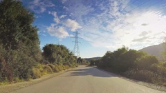 Vehicle drive hilly car travel remote narrow twisting road sunny sunlight POV Stock Footage