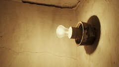 Light bulb glowing on grunge concrete wall in old house Stock Footage