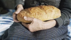Grandmother hands holding a brown loaf of bread Stock Footage