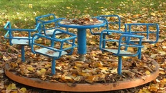 Old carousel that rotates abandoned in a park in autumn, full of leaves Stock Footage