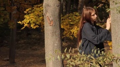 A girl touching a tree with her hands and scrutinizing the bark Stock Footage