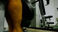 Man workout in a gym. Closeup of male feet pulling weight machine Stock Footage
