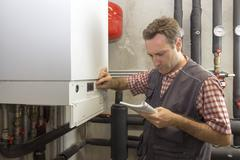 Plumber who carries out the maintenance of a condensing boiler Stock Photos