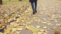 Woman walking through leaves. autumn Park Stock Footage