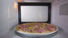 Frozen uncooked ham pizza defrosting in the microwave oven inside view Stock Footage