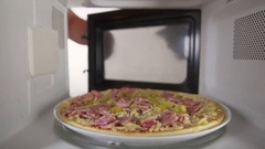 Man defrosting uncooked ham and cheese pizza in the microwave oven at home Stock Footage