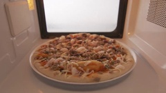 Defrosting frozen seafood pizza Frutti di Mare in microwave oven Stock Footage