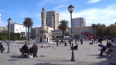 Young and old people on the Izmir Clock tower square Stock Footage