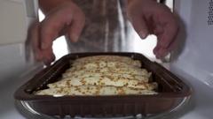 Man cooking breakfast heating pancake rolls in microwave oven Stock Footage