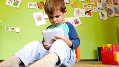 Cute little boy playing game on tablet computer in a colourful room Stock Footage