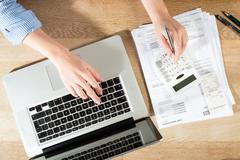 Doing Accounts at desk with Pen, Calculator and Laptop Stock Photos