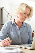 Woman Looks with Concern at Computer While Accounting at Home Stock Photos