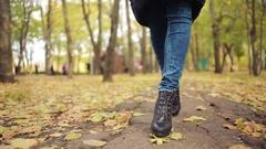 Woman walking through leaves. autumn Park Stock Footage